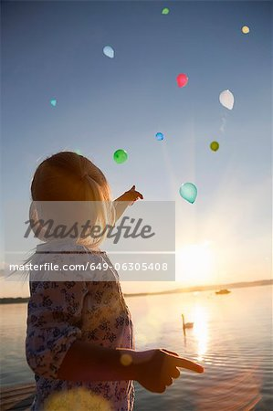 Girl watching balloons floating away Stock Photo - Premium Royalty-Free, Image code: 649-06305408