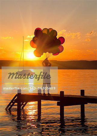 Boy holding balloons on wooden dock Stock Photo - Premium Royalty-Free, Image code: 649-06305409