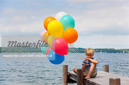 Boy holding balloons on wooden pier Stock Photo - Premium Royalty-Free, Image code: 649-06305418