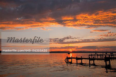 Sun setting over still rural lake Stock Photo - Premium Royalty-Free, Image code: 649-06305430