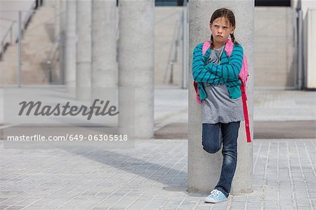 Frowning girl leaning against column Stock Photo - Premium Royalty-Free, Image code: 649-06305518