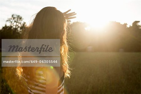 Woman shielding her eyes from sun Stock Photo - Premium Royalty-Free, Image code: 649-06305544