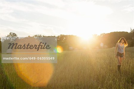 Smiling woman walking in grassy field Stock Photo - Premium Royalty-Free, Image code: 649-06305549
