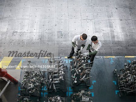 High angle view of engineers inspecting press parts in car factory Stock Photo - Premium Royalty-Free, Image code: 649-06305682