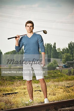 Man playing golf on train tracks Stock Photo - Premium Royalty-Free, Image code: 649-06305710