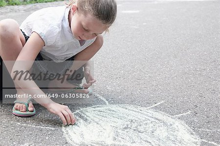 Girl drawing sun on sidewalk in chalk Stock Photo - Premium Royalty-Free, Image code: 649-06305826