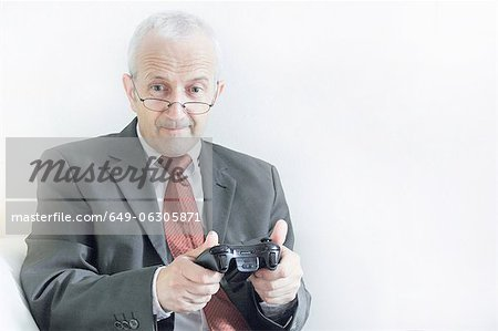 Businessman playing video games Stock Photo - Premium Royalty-Free, Image code: 649-06305871