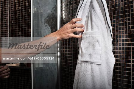 Man reaching for bathrobe in shower Stock Photo - Premium Royalty-Free, Image code: 649-06305924
