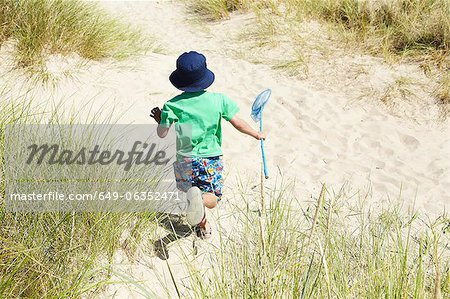Boy carrying fishing net on beach Stock Photo - Premium Royalty-Free, Image code: 649-06352471