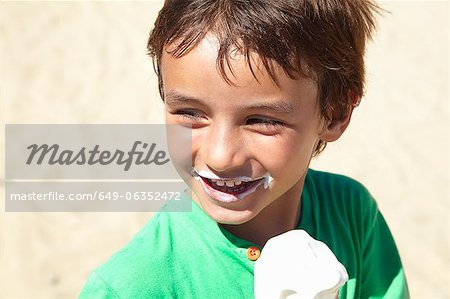 Boy eating ice cream on beach Stock Photo - Premium Royalty-Free, Image code: 649-06352472