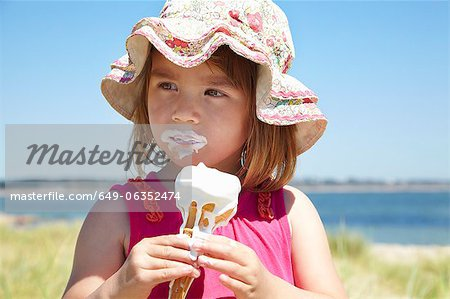 Girl eating ice cream on beach Stock Photo - Premium Royalty-Free, Image code: 649-06352474