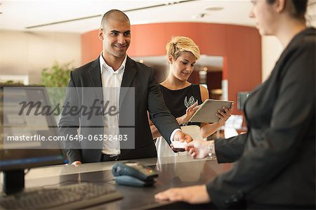 Businessman checking into hotel Stock Photo - Premium Royalty-Free, Image code: 649-06352483