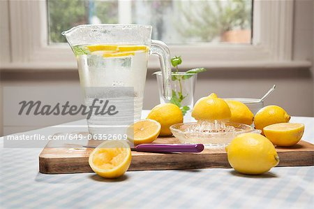 Lemons, juicer and pitcher of water Stock Photo - Premium Royalty-Free, Image code: 649-06352609