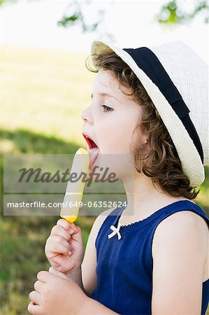 Girl eating popsicle outdoors Stock Photo - Premium Royalty-Free, Image code: 649-06352624
