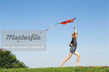 Girl playing with kite outdoors Stock Photo - Premium Royalty-Free, Image code: 649-06352630