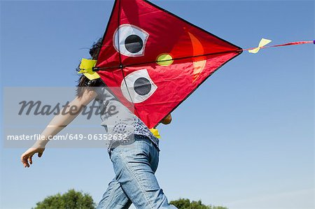 Girl playing with kite outdoors Stock Photo - Premium Royalty-Free, Image code: 649-06352632