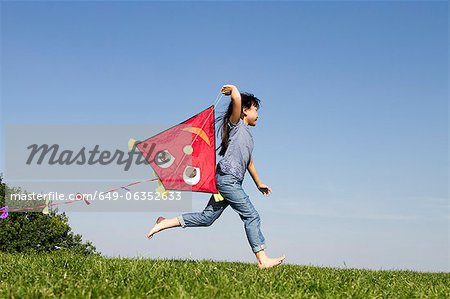 Girl playing with kite outdoors Stock Photo - Premium Royalty-Free, Image code: 649-06352633