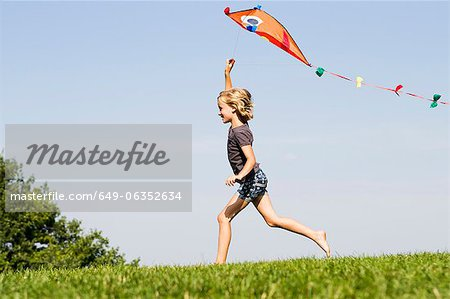 Girl playing with kite outdoors Stock Photo - Premium Royalty-Free, Image code: 649-06352634