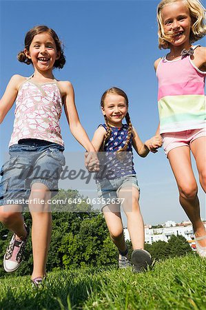 Girls running together in field Stock Photo - Premium Royalty-Free, Image code: 649-06352637