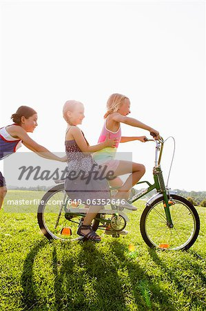 Girls playing with bicycle in grass Stock Photo - Premium Royalty-Free, Image code: 649-06352646