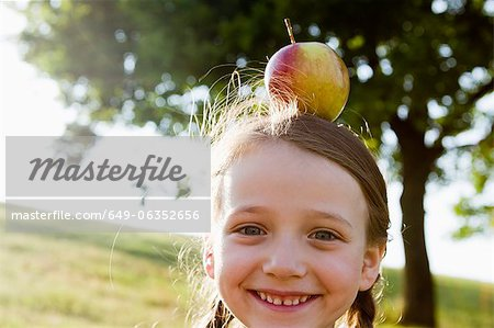 Smiling girl balancing apple on head Stock Photo - Premium Royalty-Free, Image code: 649-06352656