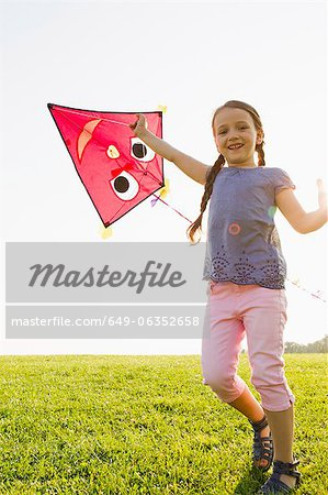 Girl playing with kite outdoors Stock Photo - Premium Royalty-Free, Image code: 649-06352658