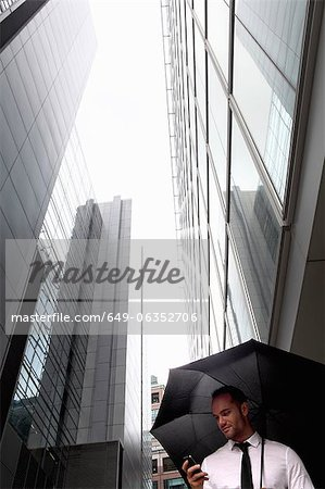 Businessman walking under umbrella Stock Photo - Premium Royalty-Free, Image code: 649-06352706