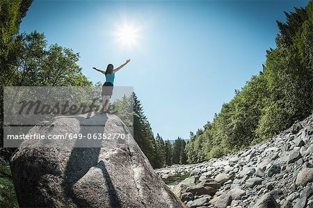 Woman with arms outstretched on rock Stock Photo - Premium Royalty-Free, Image code: 649-06352770