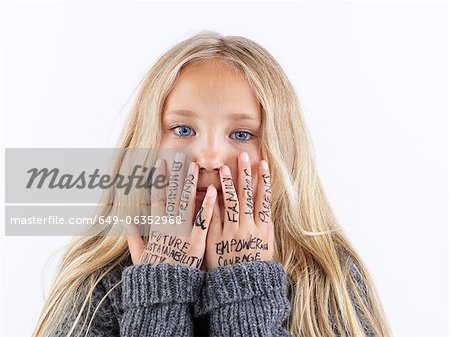 Girl covering face with writing on hands Stock Photo - Premium Royalty-Free, Image code: 649-06352968