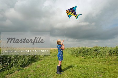 Girl flying kite in rural field Stock Photo - Premium Royalty-Free, Image code: 649-06353000