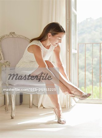 Woman putting on shoes Stock Photo - Premium Royalty-Free, Image code: 649-06353225