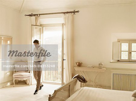 Businessman having wine in bedroom Stock Photo - Premium Royalty-Free, Image code: 649-06353248