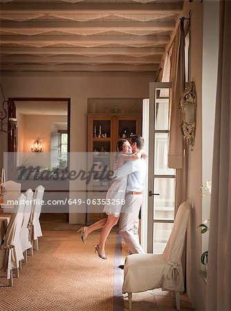 Couple hugging in dining room Stock Photo - Premium Royalty-Free, Image code: 649-06353258