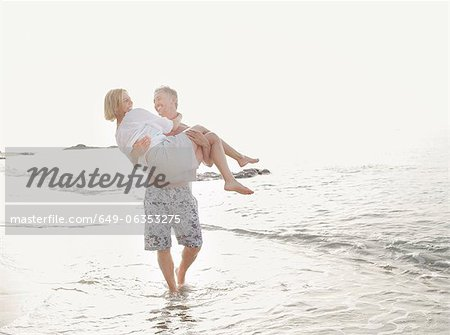 Man carrying wife in waves on beach Stock Photo - Premium Royalty-Free, Image code: 649-06353275