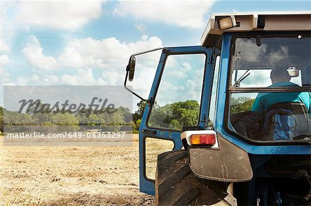 Farmer sitting in tractor in crop field Stock Photo - Premium Royalty-Free, Image code: 649-06353297