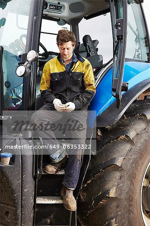 Farmer using cell phone on tractor Stock Photo - Premium Royalty-Free, Image code: 649-06353322