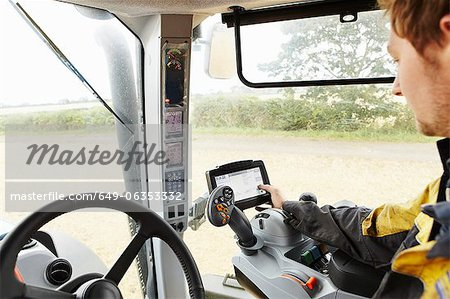 Farmer driving tractor in field Stock Photo - Premium Royalty-Free, Image code: 649-06353332