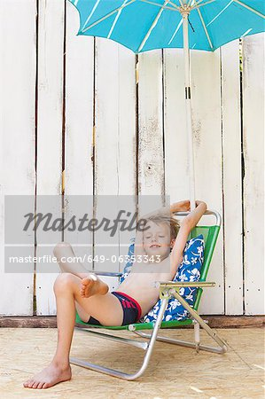 Boy in swimsuit in lawn chair indoors Stock Photo - Premium Royalty-Free, Image code: 649-06353343