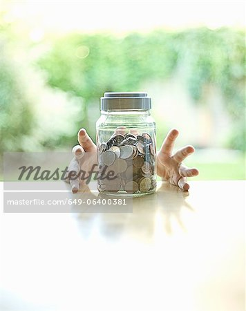Hands grabbing jar of change Stock Photo - Premium Royalty-Free, Image code: 649-06400381