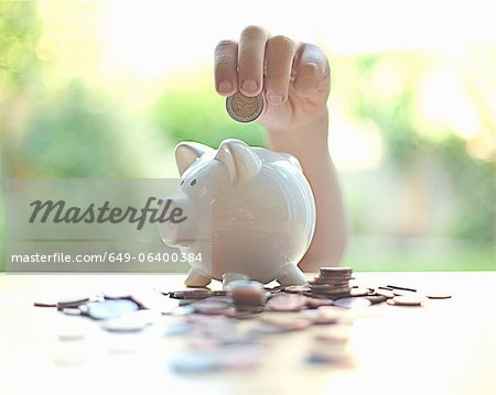 Hang putting coins in piggy bank Stock Photo - Premium Royalty-Free, Image code: 649-06400384