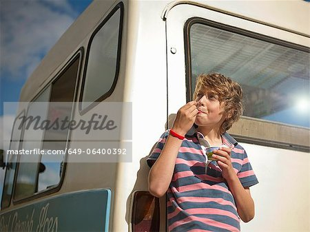 Boy eating ice cream by truck Stock Photo - Premium Royalty-Free, Image code: 649-06400392
