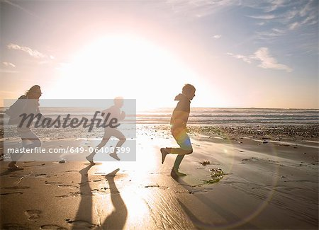 Family running together on beach Stock Photo - Premium Royalty-Free, Image code: 649-06400399