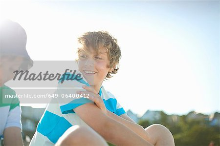 Smiling boys sitting outdoors Stock Photo - Premium Royalty-Free, Image code: 649-06400412