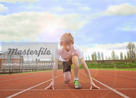 Boy crouched at starting line on track Stock Photo - Premium Royalty-Free, Image code: 649-06400417