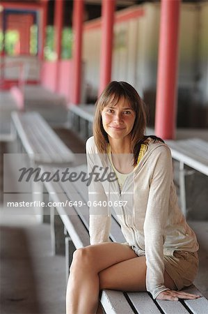 Smiling woman sitting on bench Stock Photo - Premium Royalty-Free, Image code: 649-06400657