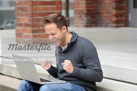 Man using laptop and cheering Stock Photo - Premium Royalty-Free, Image code: 649-06400691
