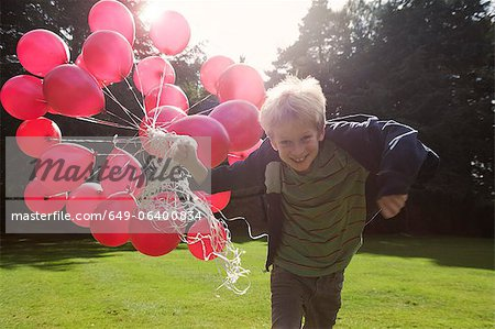 Boy carrying bunch of balloons outdoors Stock Photo - Premium Royalty-Free, Image code: 649-06400834