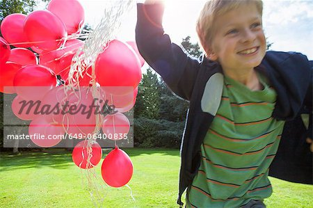 Boy carrying bunch of balloons outdoors Stock Photo - Premium Royalty-Free, Image code: 649-06400835