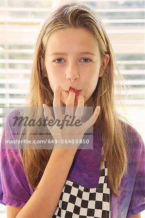 Girl tasting cake frosting in kitchen Stock Photo - Premium Royalty-Free, Image code: 649-06400850