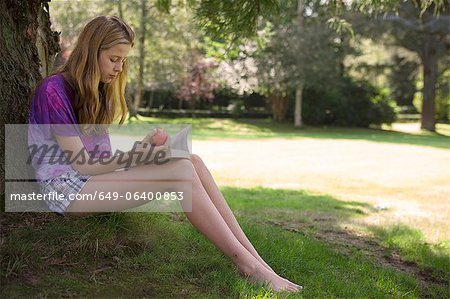 Girl eating apple and reading in park Stock Photo - Premium Royalty-Free, Image code: 649-06400853